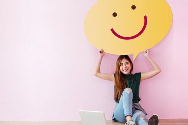 girl sitting on floor holding smile sign