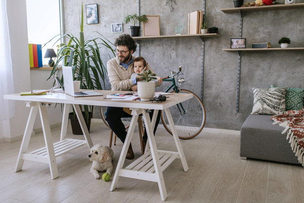 man working remotely with baby and dog