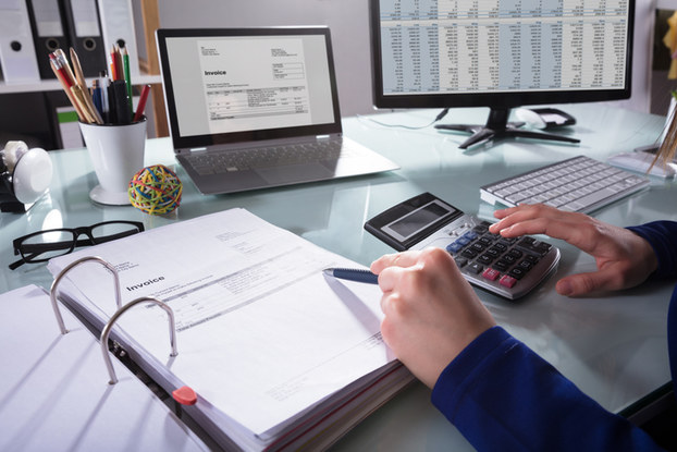 person doing finances with calculator and computer