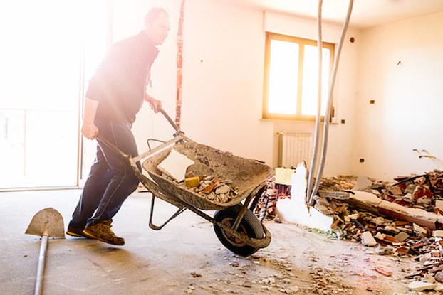 man with wheelbarrow in damaged building