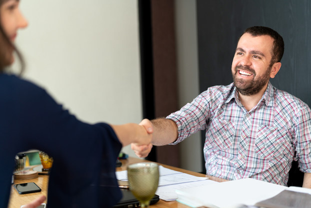 man shaking hands with woman at interview