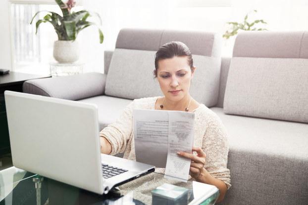 woman looking at paperwork and laptop