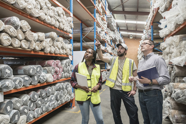 three people in a factory looking at goods on shelves