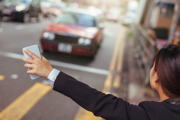 girl hailing uber with phone