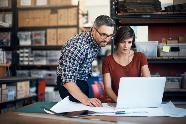 man and woman at work looking at a laptop