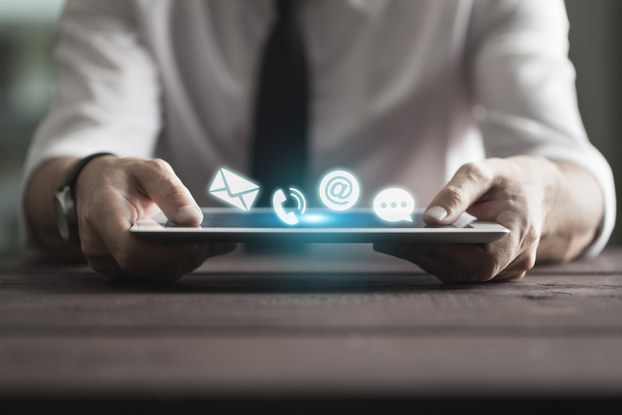 man holding tablet with communication icons