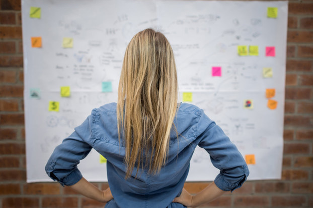 woman looking at whiteboard with notes