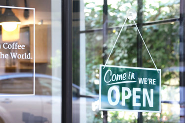 open business sign hanging on glass door