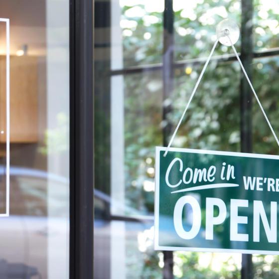 open business sign hanging on glass door