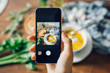 woman holding phone taking picture of soup