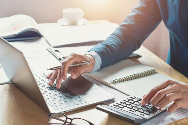 man using laptop and calculator