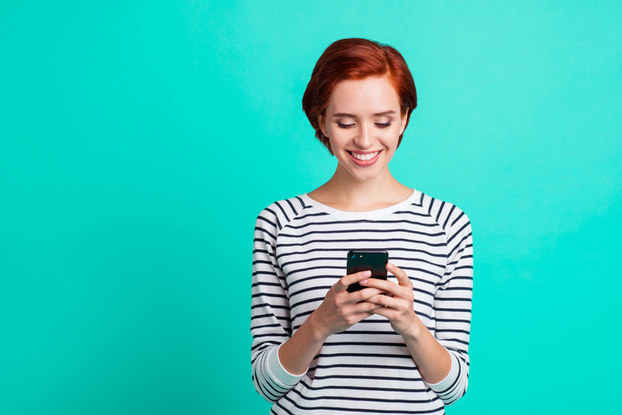 woman smiling while holding phone