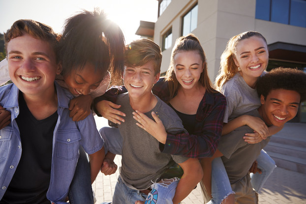 group of teens hugging and laughing
