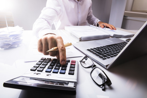 person sitting at desk with laptop and calculator