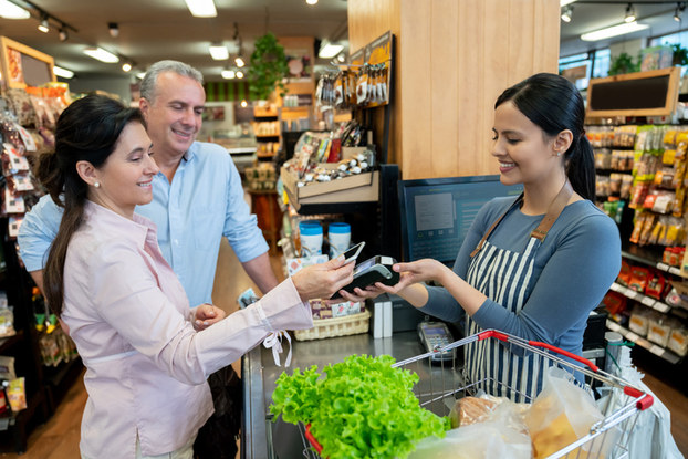woman paying for groceries with smartphone