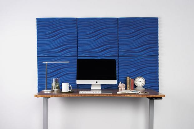 uplift desk's acoustic 3d wave wall panel behind computer desk