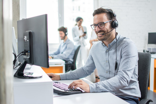 male employee on headset and computer