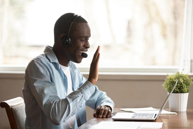man working remotely waving to laptop screen