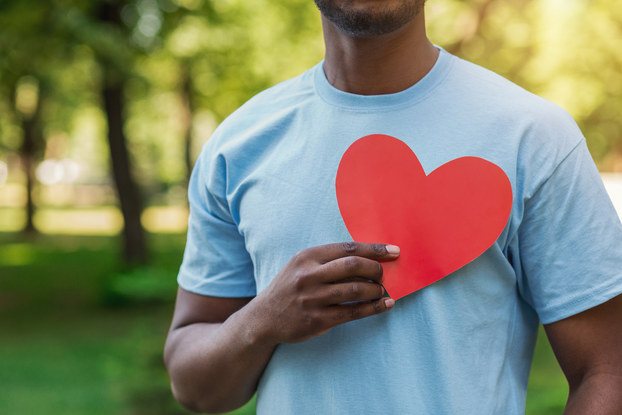 volunteer holding cutout heart to chest