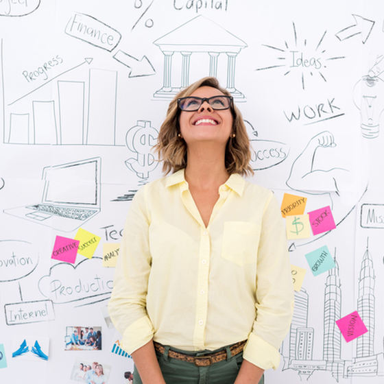 woman standing in front of whiteboard brainstorming