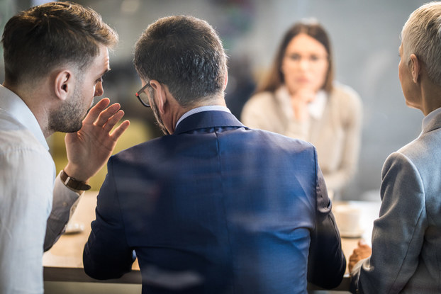 professionals in a meeting whispering