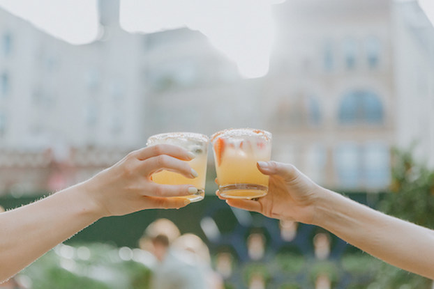 two hands holding margaritas doing cheers