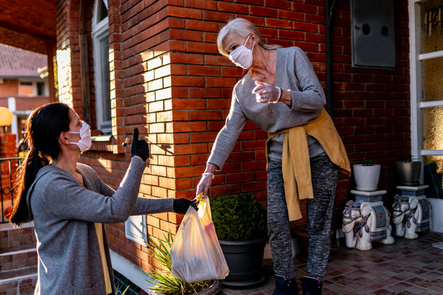 woman delivering groceries to another woman with masks on