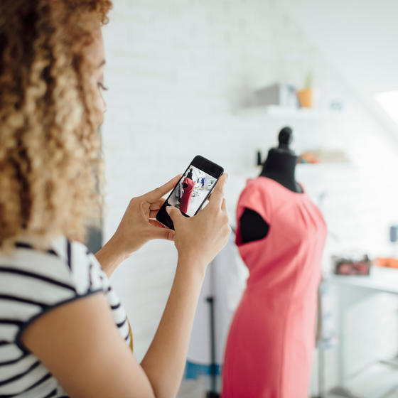 woman seamstress taking photo of dress on a mannequin