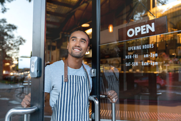 small business owner holding door to business open