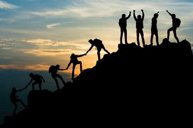 people helping each other climb a mountain
