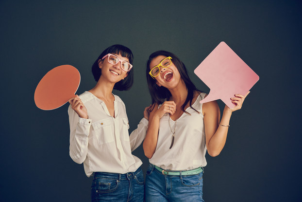 two women holding cutouts of speech boxes