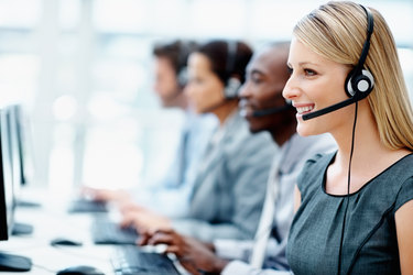 team of salespeople sitting in a row on headsets