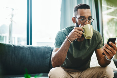 man drinking coffee looking at cellphone
