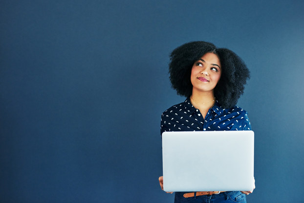woman smiling and thinking while holding a laptop