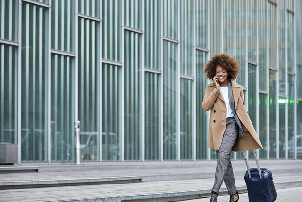 businesswoman on phone walking with suitcase