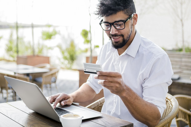 man paying for something on laptop with credit card
