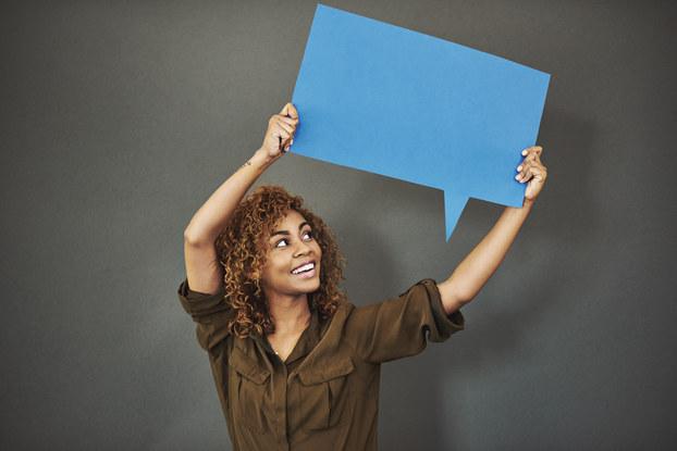 woman standing holding speech bubble