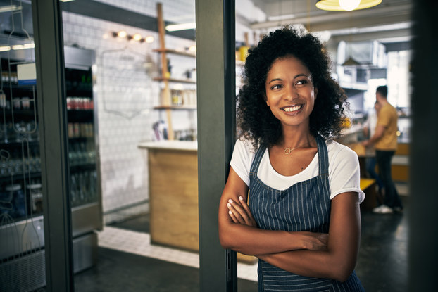 woman in apron standing outside cafe