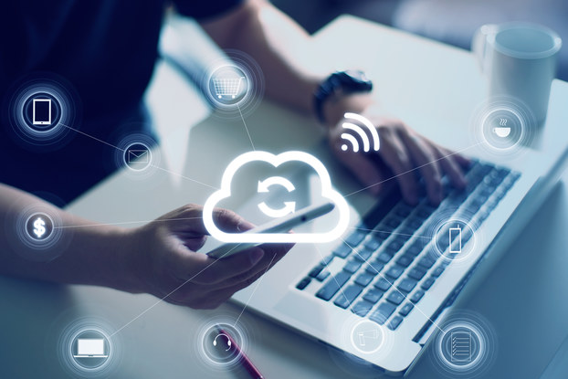 person on laptop and phone with cloud storage icons