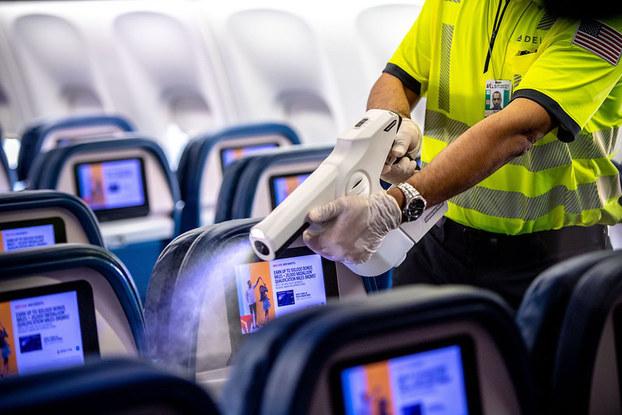 worker on delta plane using sanitizer machine
