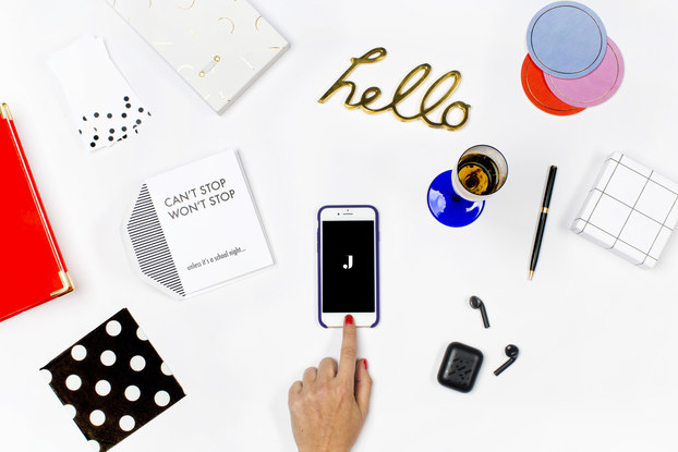 jetblack's branding spread on a white desk with phone