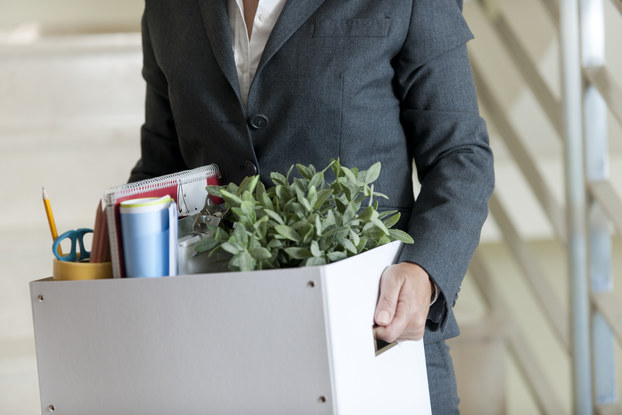 man in suit with packed box of office belongings