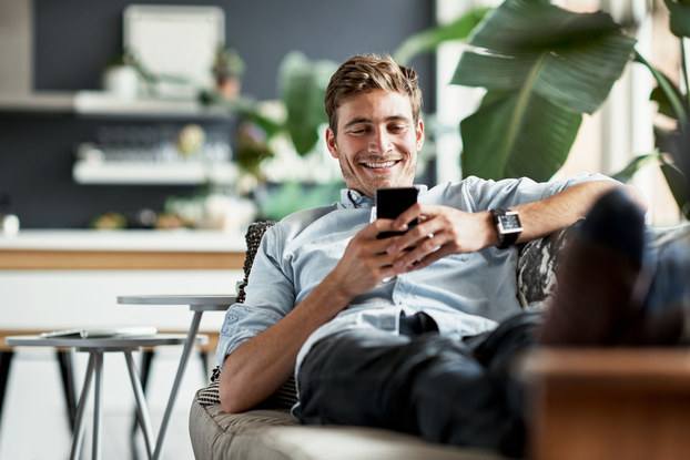man relaxing on couch with phone