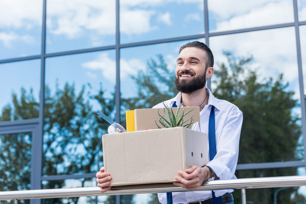man holding box with office things after quitting job