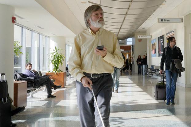 man with cane using indoor explorer app
