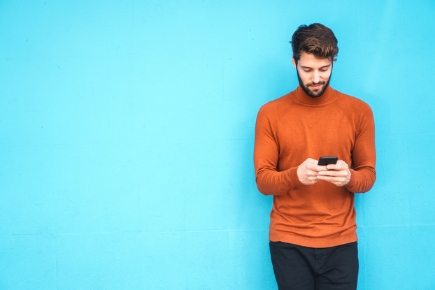 man standing looking down at phone