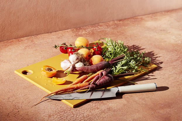 material kitchen knife and cutting board with vegetables