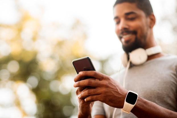 man wearing headphones looking at smartphone