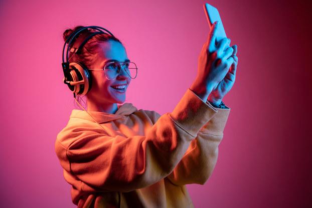 woman with headphones taking selfie