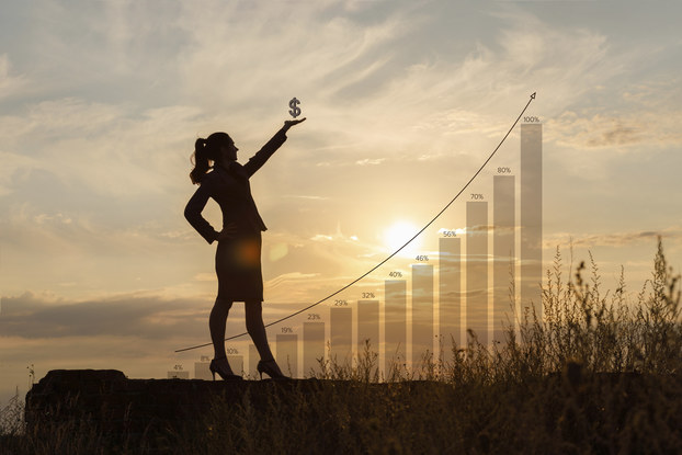 woman standing in front of a graph with increasing money